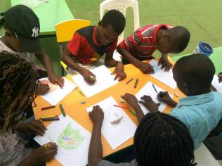 Students at Bellanoor International Community School, Nigeria, designing their school business' logo